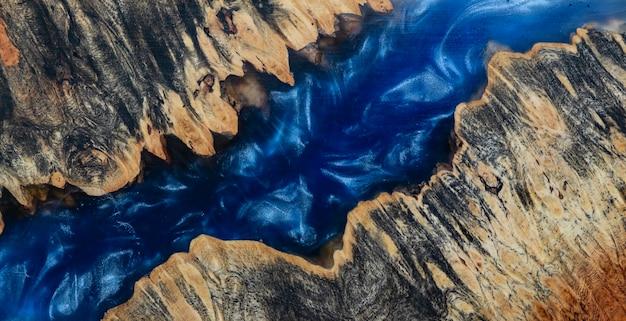 Gießen von epoxidharz stabilisierende maser afzelia holz blauer hintergrund