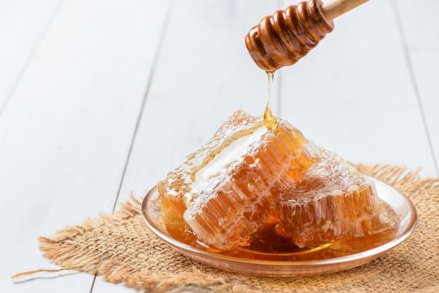 Gießen von frischem honig in waben auf teller, weißem holztisch, bienenprodukte durch organisches natürliches zutatenkonzept