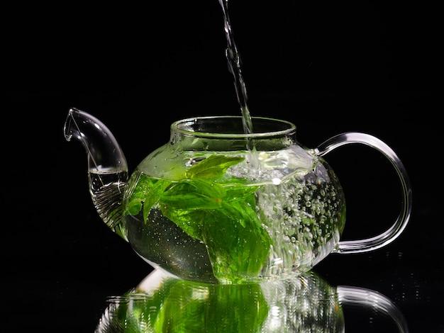 Gießen von heißem wasser in eine glasteekanne auf schwarzem hintergrund grüner minztee kräutertee und gesund
