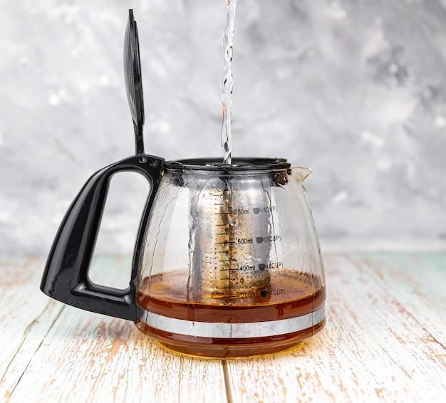 Gießen von heißem wasser in eine teekanne mit schwarzem tee auf holztisch