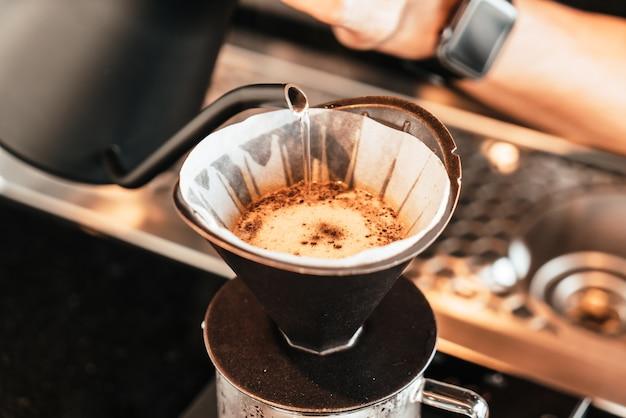 Gießen von heißem wasser zum abtropfen von arabica-kaffee