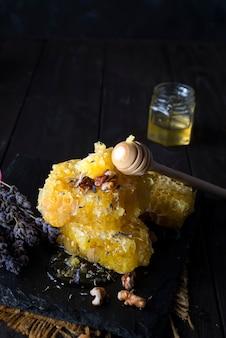 Gießen von honig in honigkamm mit walnüssen und lavendelblüten auf dunklem steinhintergrund