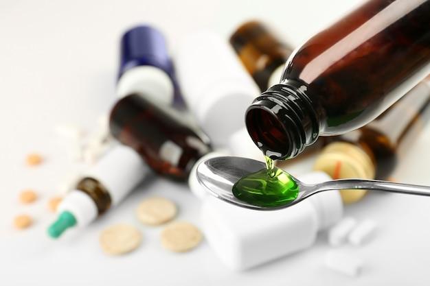 Gießen von hustensaft in löffel auf verschwommenem hintergrund von medikamenten