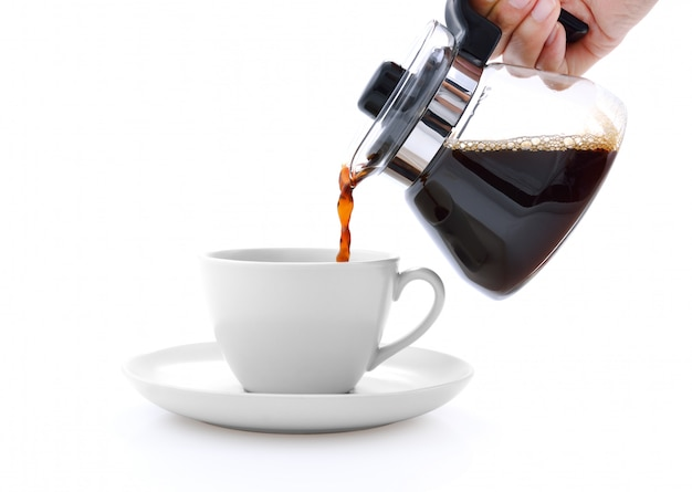 Gießen von kaffee auf eine tasse lokalisiert auf weißem hintergrund