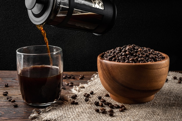 Gießen von kaffee aus einer französischen presse in die tasse auf dunklem hintergrund.