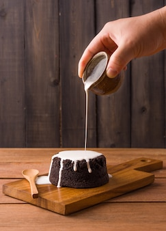 Gießen von milchsauce auf schokoladenbrownies auf holzteller und holzhintergrund. hausgemachte bäckerei und dessert
