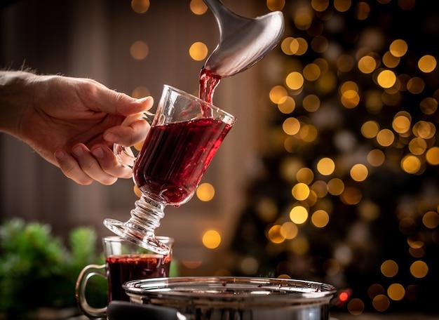 Gießen von rotem glühwein in transparentes glas, das von mann auf weihnachtsbeleuchtung gehalten wird