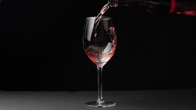 Gießen von rotwein aus einer flasche in ein weinglas lokalisiert auf schwarzem hintergrund.