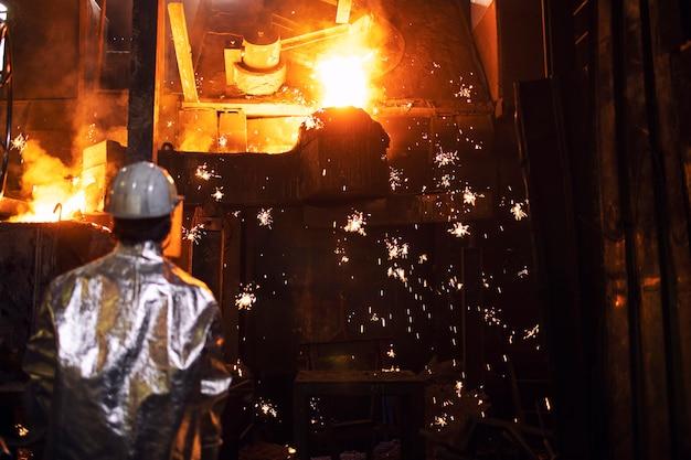 Gießereiarbeiter, der das schmelzen von eisen im ofen und die herumfliegenden funken kontrolliert.