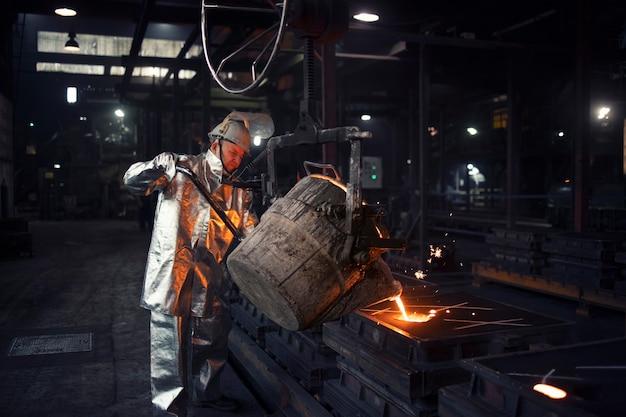 Gießereiarbeiter, der flüssigen stahl in formen gießt.