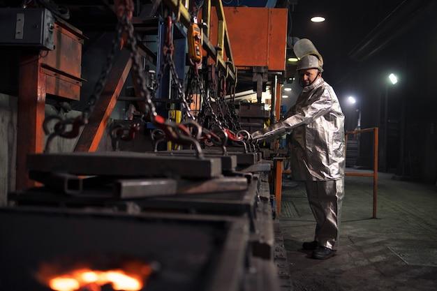 Gießereiarbeiter, der formen für heißen geschmolzenen stahl vorbereitet.