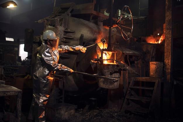 Gießereiarbeiter, der geschmolzenen stahl im brennenden ofen prüft.