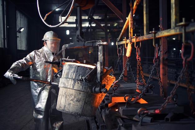 Gießereiarbeiter, der mit heißem stahl, metallurgie und schwerindustrie arbeitet.