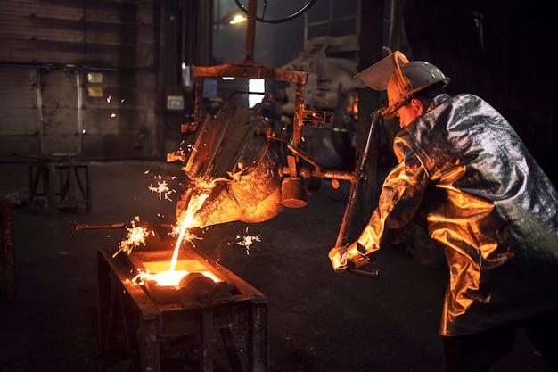 Gießereiarbeiter in schutzanzug und helm, der form mit heißem geschmolzenem eisen füllt, um teile für die industrie herzustellen.