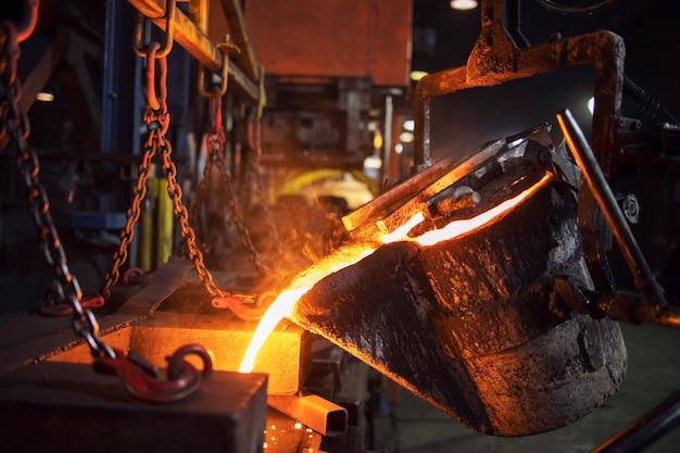 Gießereikübel, der heißes geschmolzenes metall in eine gießform für die mettalurgie und stahlproduktion gießt.