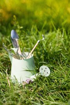 Gießkanne und gartengeräte auf gras im sommer