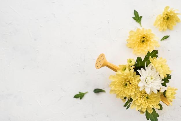 Gießkanne und strauß gelber frühlingsblumen
