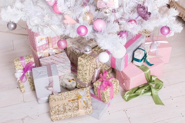 Giftboxes, rosa und weiße weihnachtsdekorationsbälle, die an einem dekorativen weißen weihnachtsbaum hängen