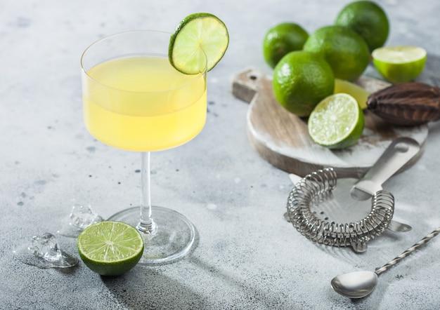Gimlet kamikaze cocktail in modernem glas mit limettenscheibe und eis auf heller oberfläche mit frischen limetten und sieb mit shaker.