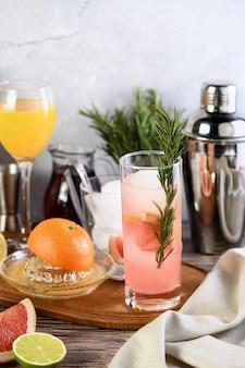 Gin-cocktail mit rosmarin und granatapfel auf einem tisch zwischen zitrusfrüchten und getränken.