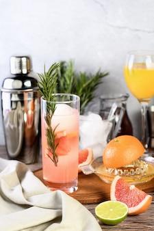 Gin cocktail mit rosmarin und granatapfel auf einem tisch zwischen zitrusfrüchten und getränken.