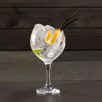 Gin tonic cocktail mit eis vanille lima und zitrone auf schwarz