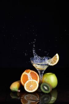 Gin tonic cocktail mit früchten, spritzern und zitrone auf isoliertem schwarz