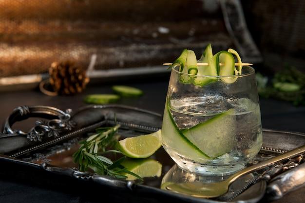 Gin & tonic im transparenten glas mit einer limettenscheibe daneben