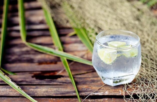 Gin tonic in glas mit eiswürfeln und limettenscheibe