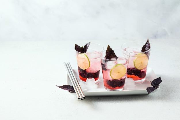 Gin tonic mit brombeeren und blättern von lila basilikum. sommer erfrischender cocktail