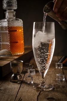Gin tonic wird in einer schüssel mit eis auf einem rustikalen tisch mit bagger, sieb, sieb und eiswürfeln serviert.