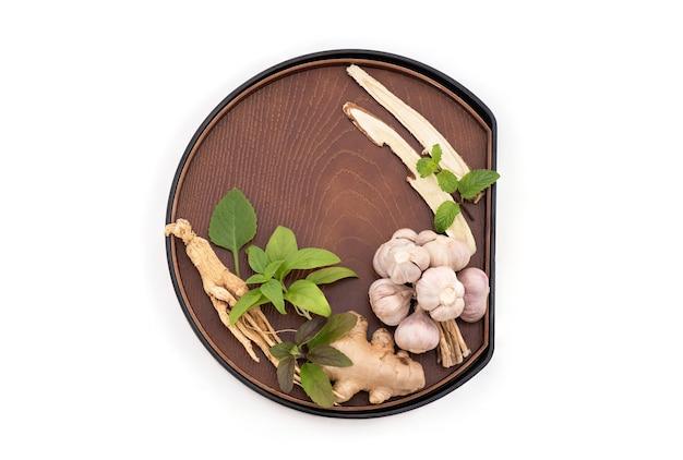 Ginseng, süßholz, ingwer, oregano, heiliges basilikum, thailändisches basilikum, knoblauch- und pfefferminzblätter einzeln auf weißem hintergrund mit beschneidungspfad, draufsicht, flach.