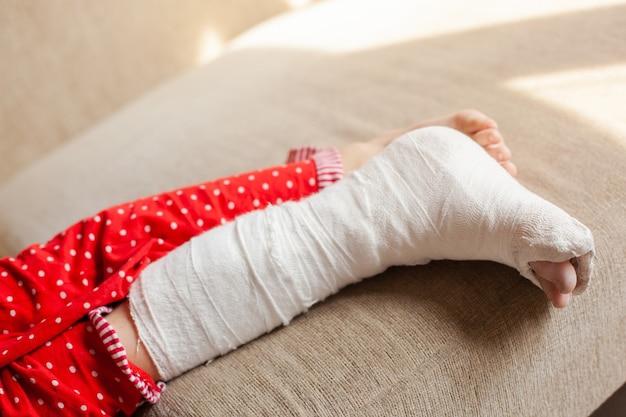 Gipsbein eines teenagers auf einem sofa nach einem unfall mit knöchelbruch