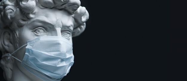 Gipsskulptur in einer medizinischen maske. konzept der coronavirus-epidemien und das risiko einer biologischen kontamination. prävention und behandlung von influenza.