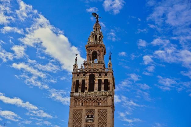 Giralda, glockenturm der kathedrale von sevilla mit einem blauen himmel im hintergrund - vertikale postkarte