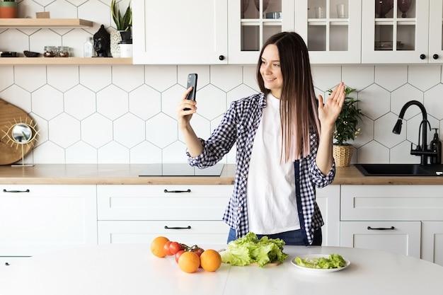 Girl food blogger führt eine live-übertragung in der küche, zeigt, wie man gesundes essen kocht