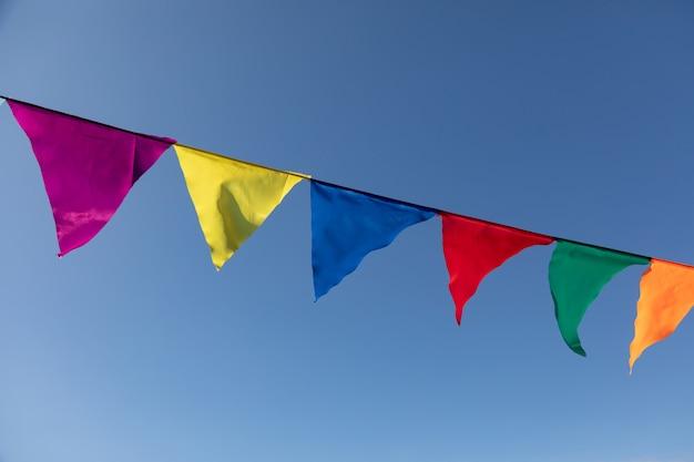 Girlande aus bunten dreieckigen flaggen, die sich im wind vor dem hintergrund des blauen himmels entwickeln. feier-party. festliche stimmung