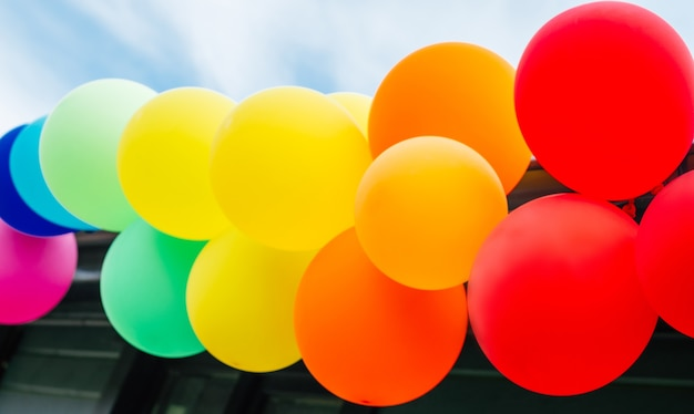 Girlande aus bunten regenbogenballons gegen blauen himmel