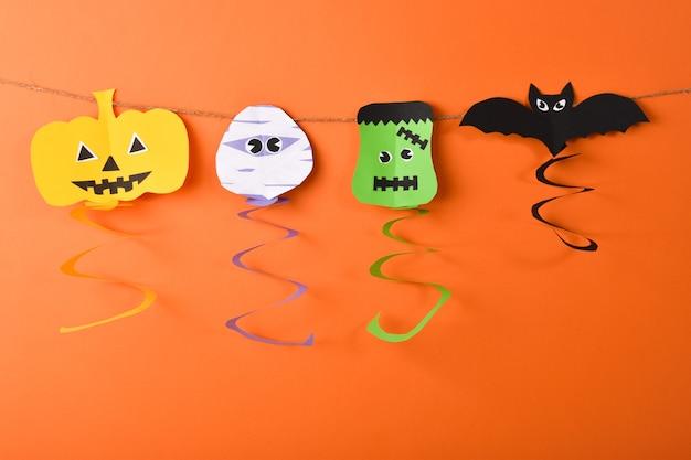Girlande aus halloween-figuren strecken sie sich auf den seilen von kürbis-zombie-fledermaus und frankenstein aus
