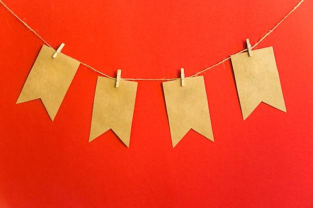 Girlande von handwerksflaggen auf wäscheklammern auf einem roten hintergrund