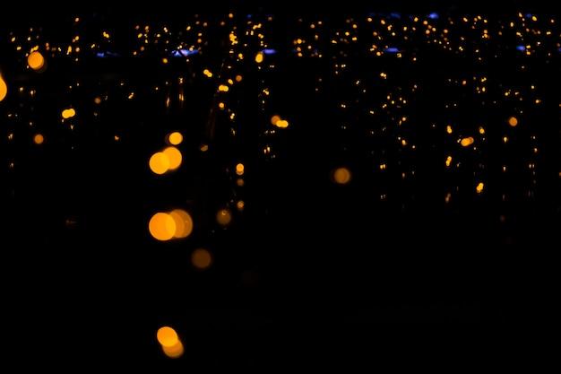 Girlanden leuchten orange und gelb am fenster