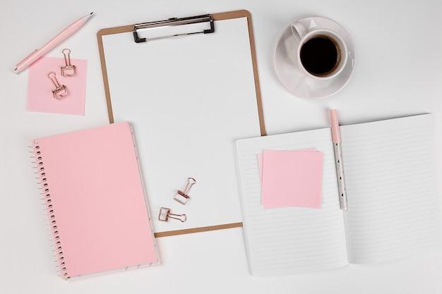 Girly schreibtisch mit leerem notizblock und kaffee