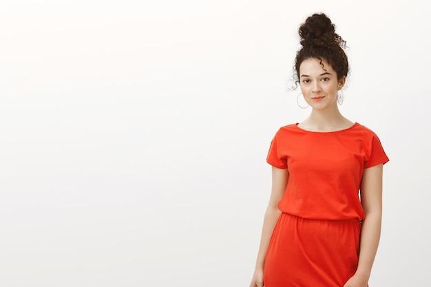 Girly stilvolle europäische frau im roten kleid mit lockigen haaren in brötchenfrisur