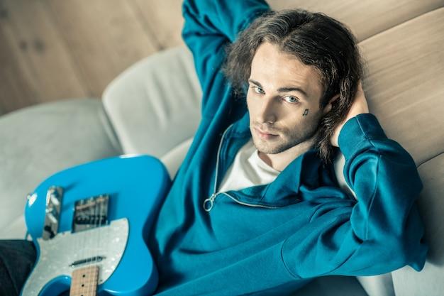 Gitarre auf den knien. hübscher junger mann, der sich ausstreckt und die hände hinter dem kopf hat, während er sich auf dem sofa entspannt