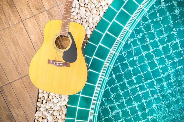 Gitarre auf hölzernem pfad neben dem swimmingpool