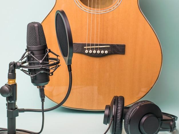 Gitarre, mikrofon und kopfhörer auf blauer oberfläche