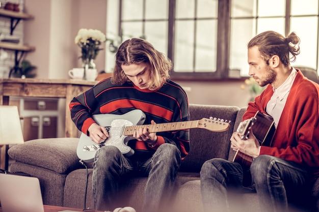 Gitarre und freund. blonder student mit bob-schnitt, der neben seinem bärtigen freund gitarre spielt