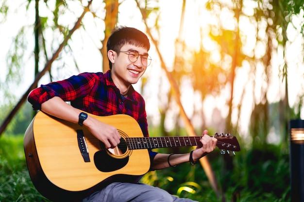 Gitarre und mann der junge gitarrist spielt die musik glücklich.