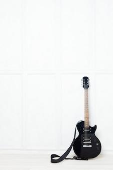 Gitarre vor einer weißen wand gestützt