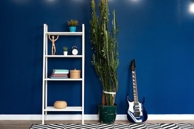 Gitarrenaufbau gegen klassische blaue wand in der wohnung